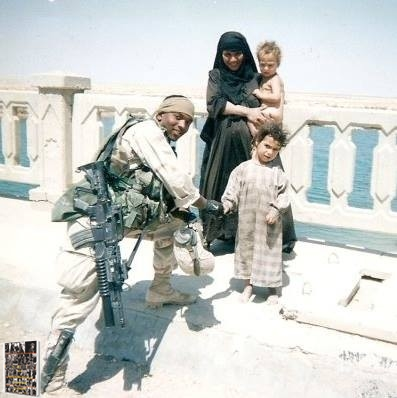 Vrail George in the Army posing with Iraqi families